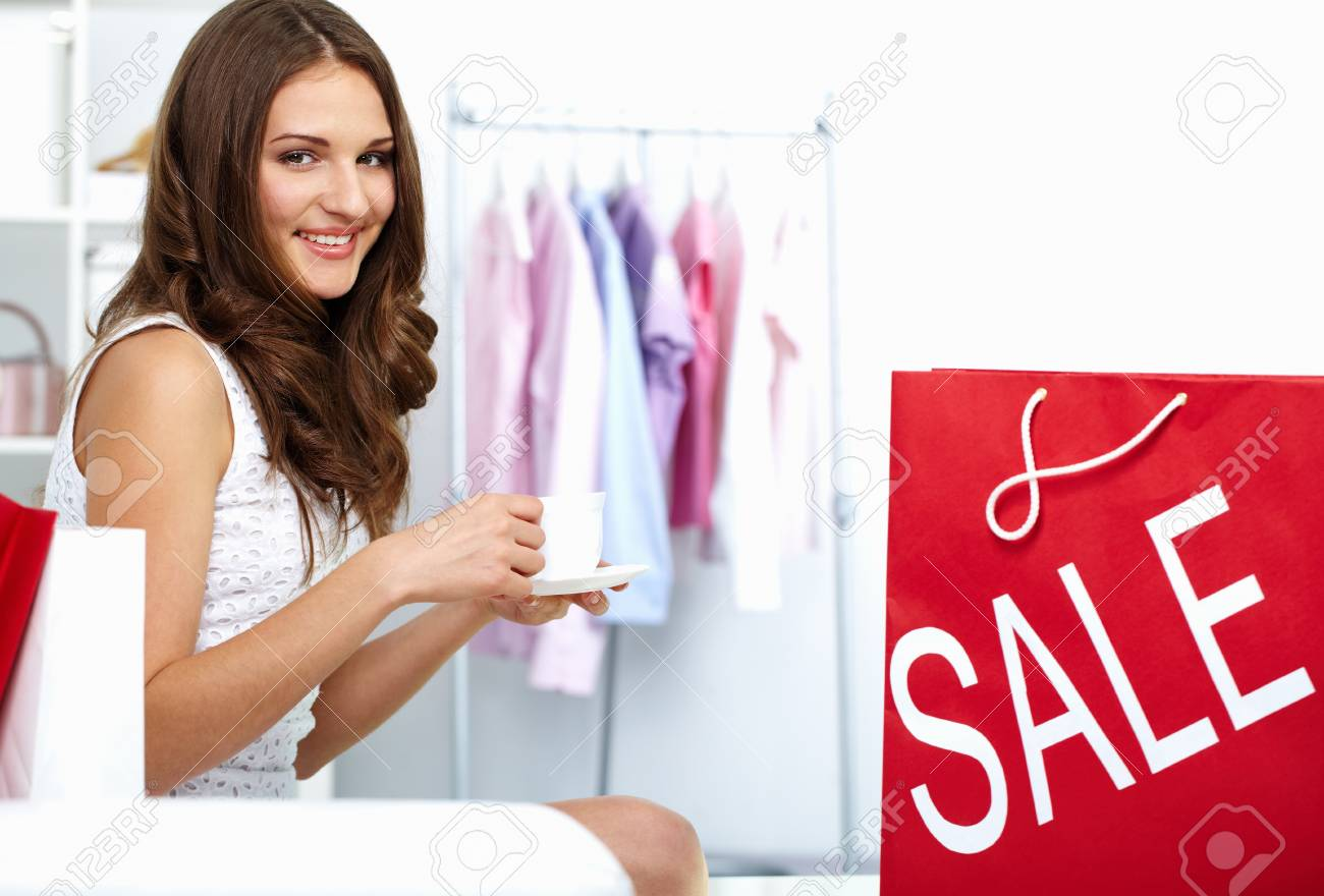 Young woman drinking coffee at shop with shopping bag from sale nearby Stock Photo - 10699956