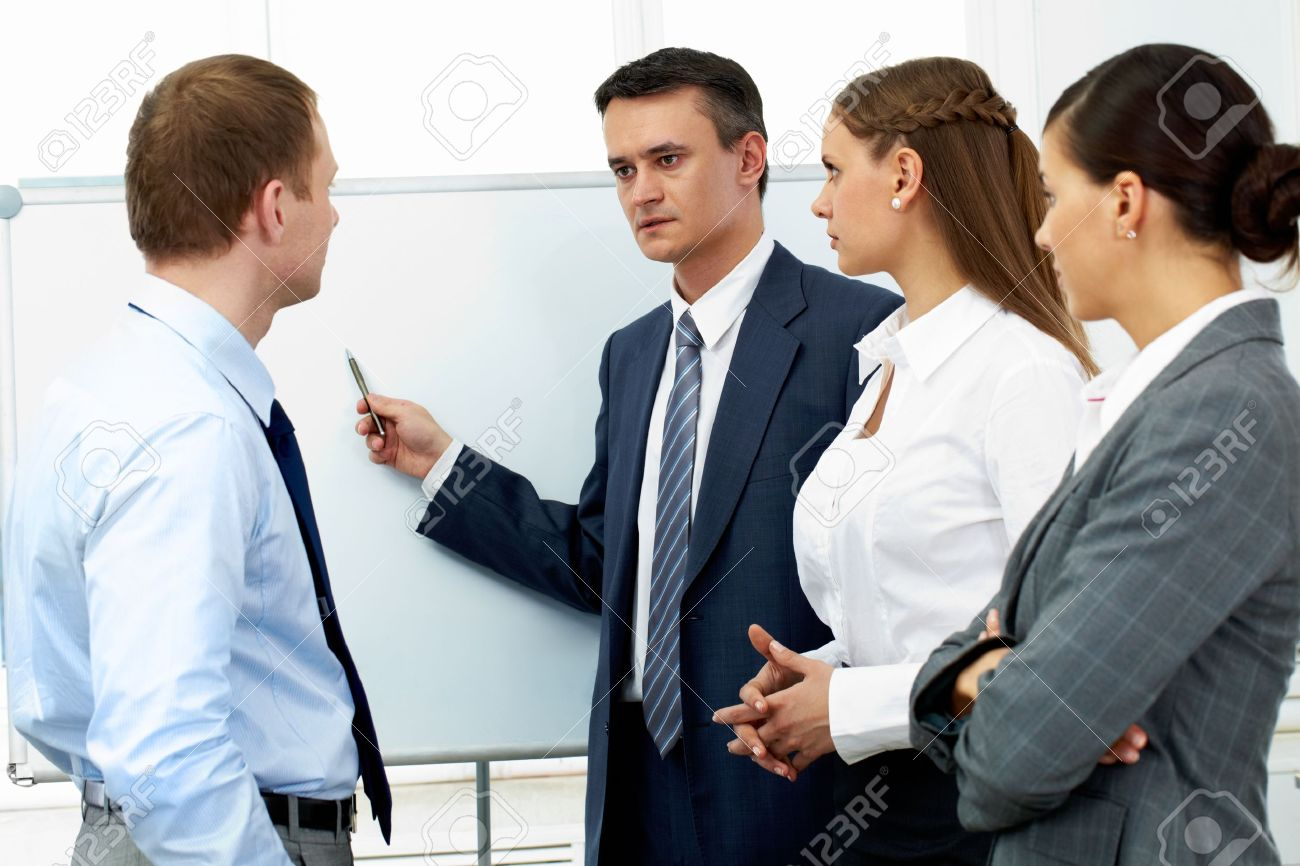 Confident boss explaining something to his colleagues Stock Photo - 10864357