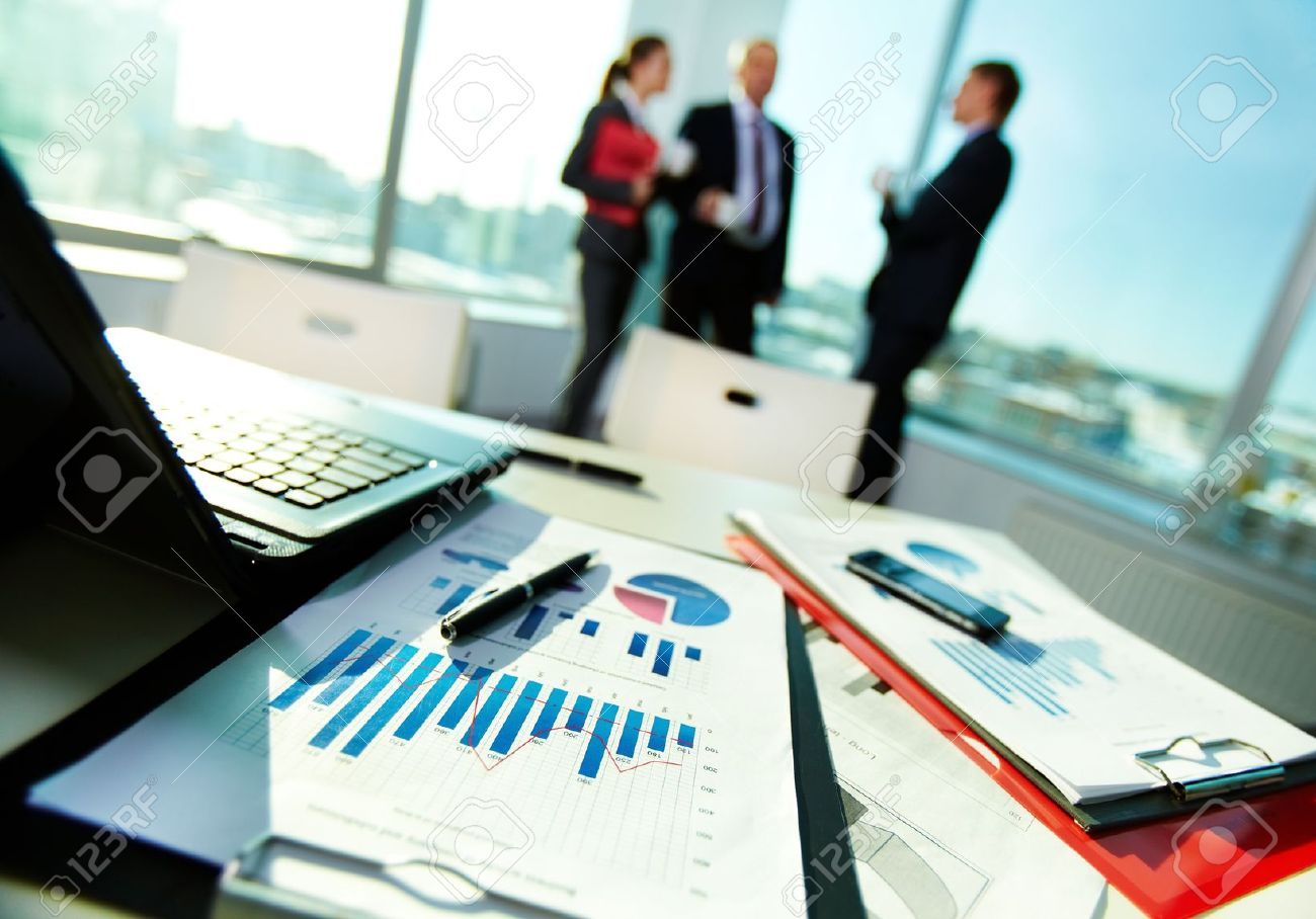 image of business documents on workplace with three partners interacting on background stock photo 11236406 - Business Documents