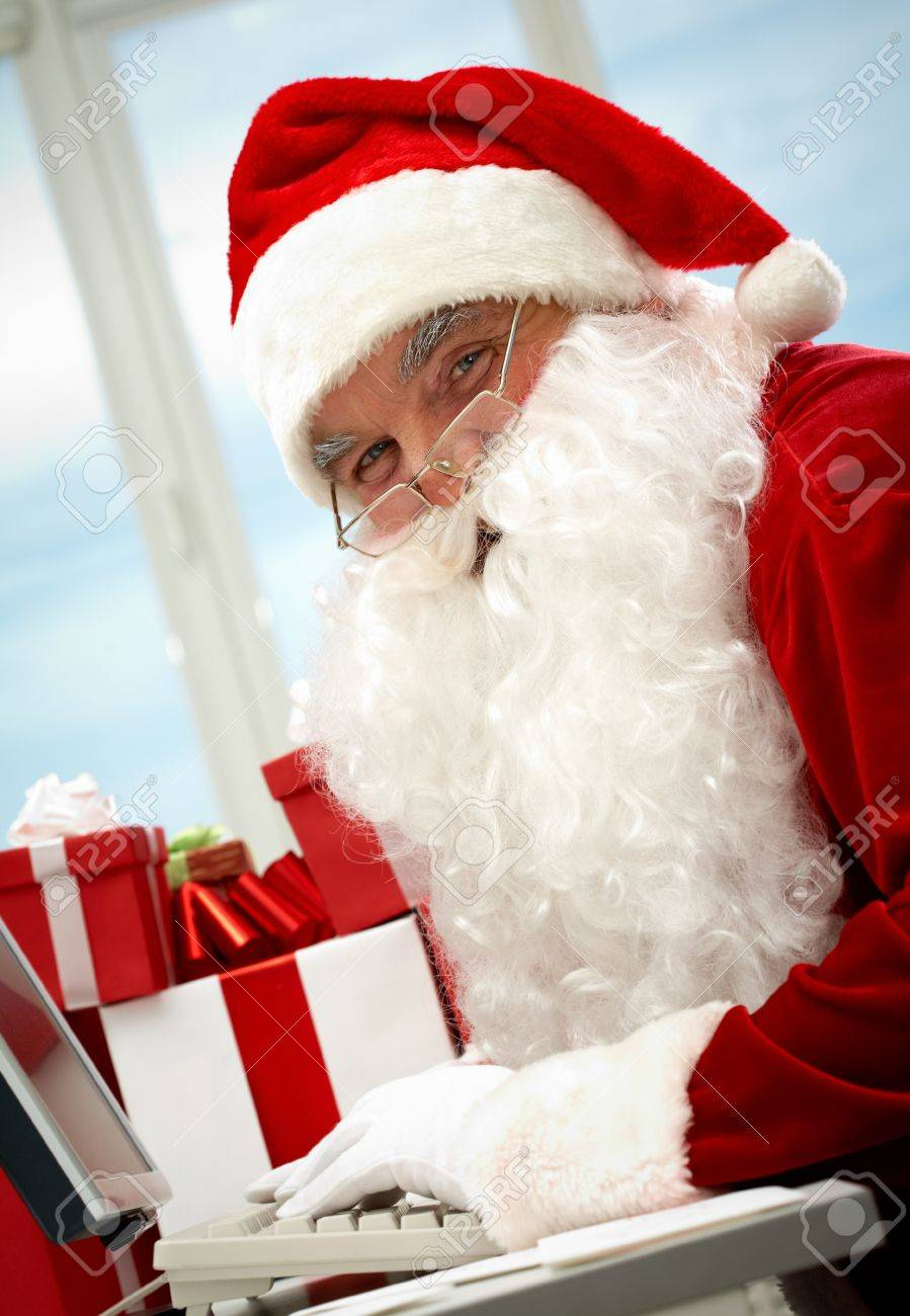 Portrait of Santa Claus typing and looking at camera Stock Photo - 11268458
