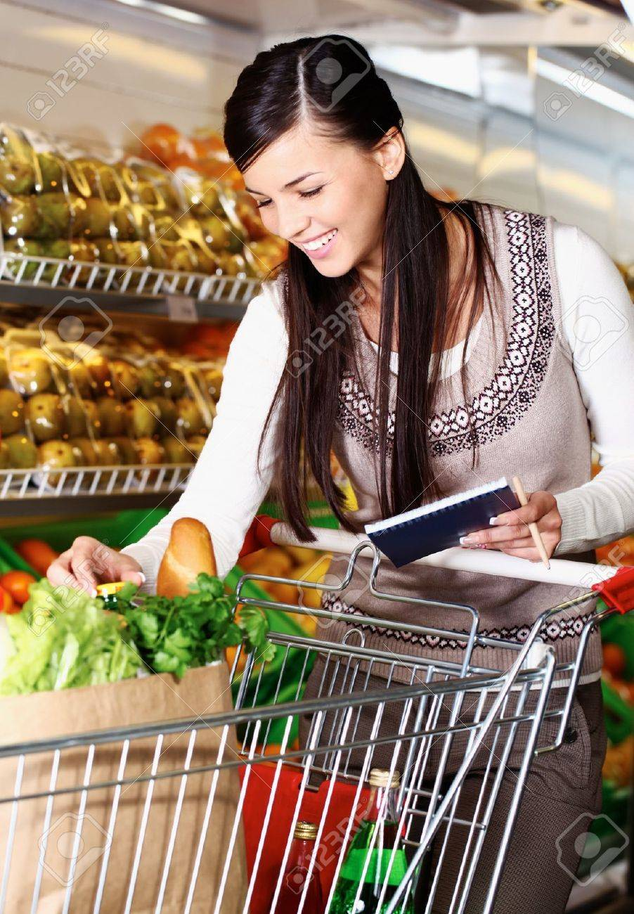 Image of pretty woman choosing products in supermarket with list of things to buy Stock Photo - 11268469