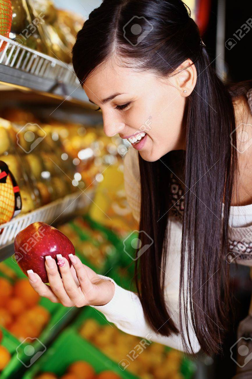 Image of happy woman with fresh apple in hand looking at it in supermarket Stock Photo - 11268450