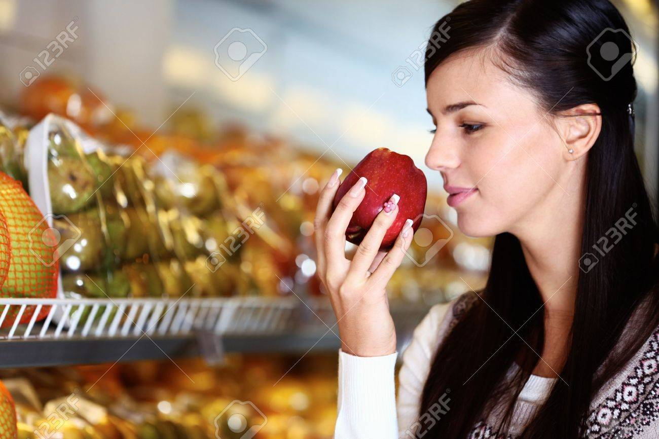 Image of young woman with fresh apple in hand smelling it in supermarket Stock Photo - 11268431