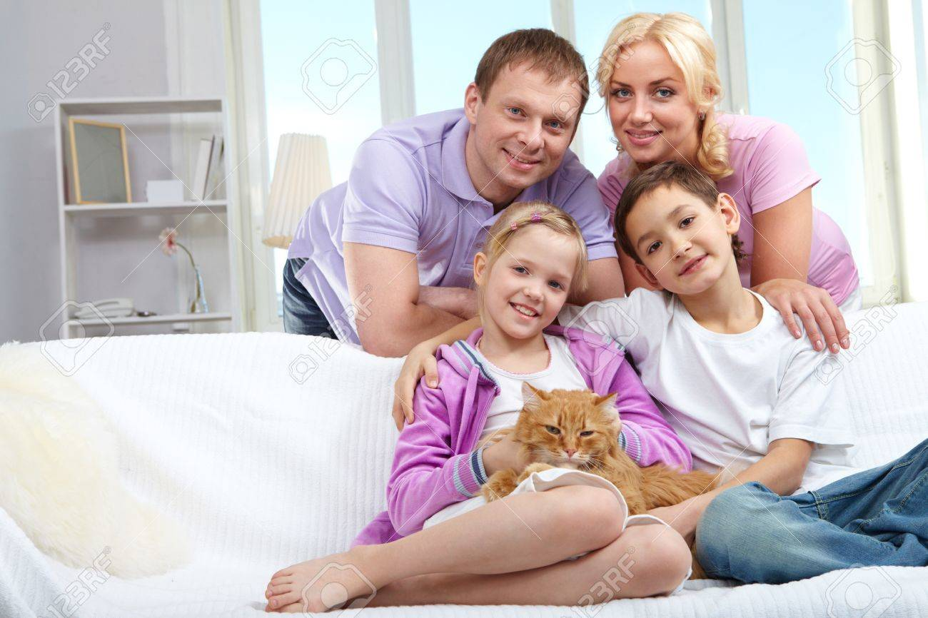 A young family of four with a cat sitting on sofa, looking at camera and smiling Stock Photo - 11425817