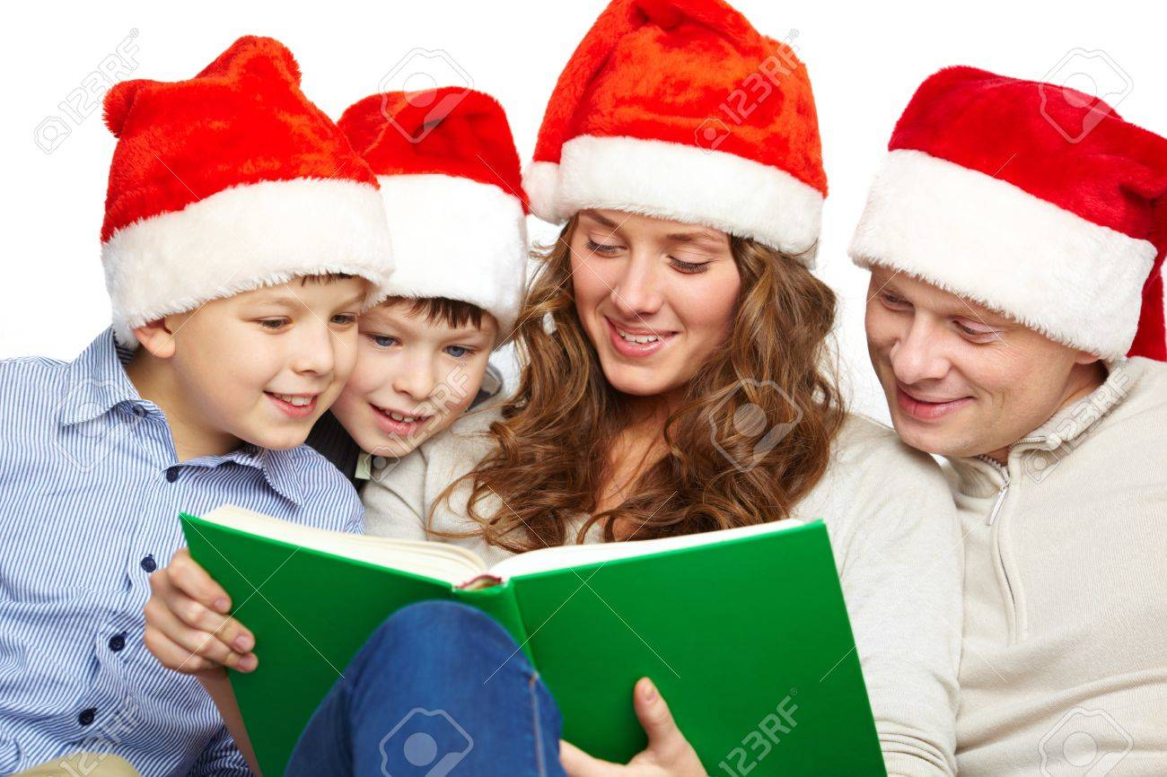 Portrait of four happy family members in Santa caps reading book Stock Photo - 11425916