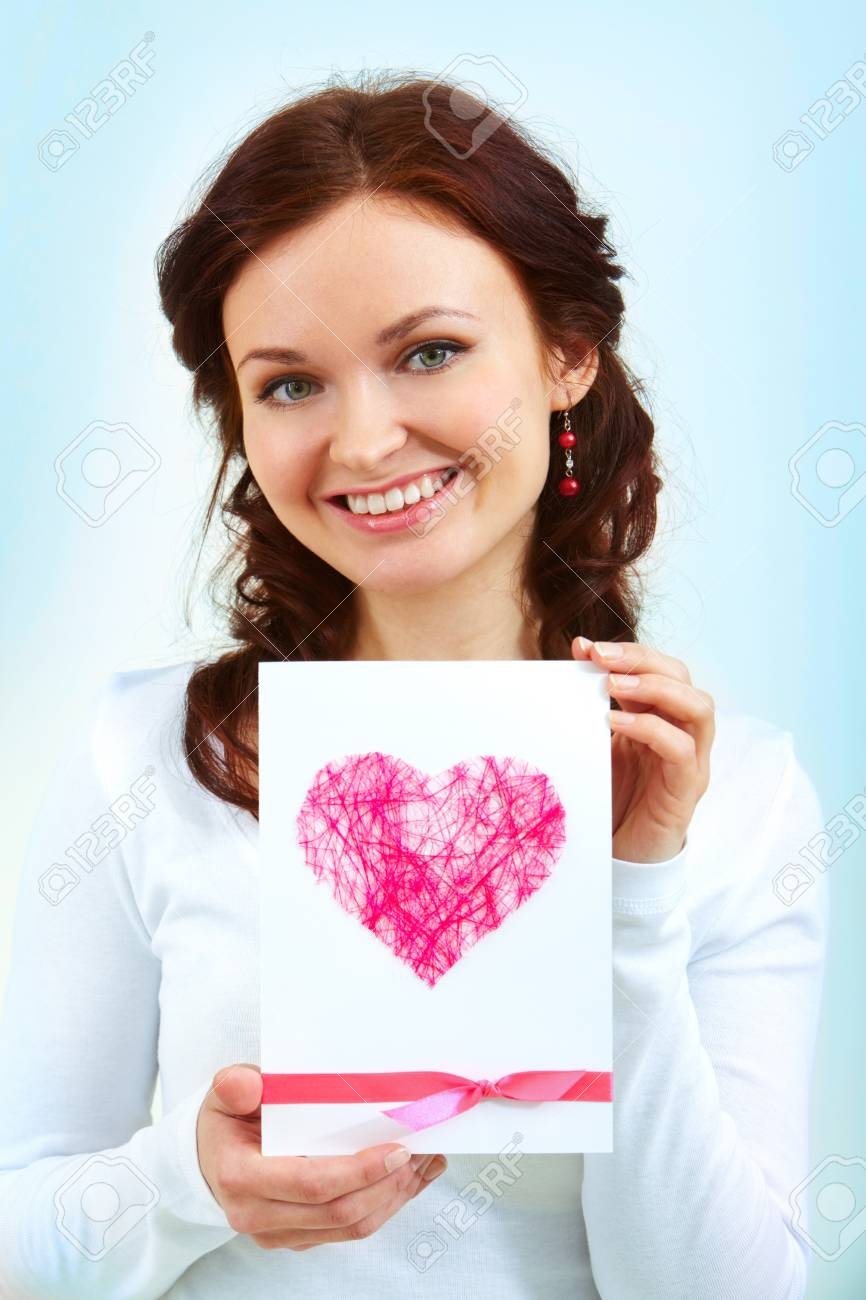 portrait of a woman holding card with pink heart stock photo