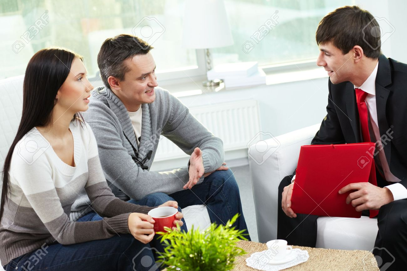 Portrait of modern couple talking to manager while discussing conditions of mortgage Stock Photo - 11920842