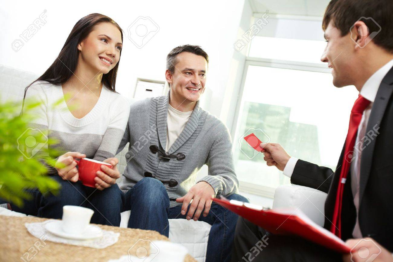 Portrait of modern couple looking at real estate agent giving his visiting card Stock Photo - 11920498