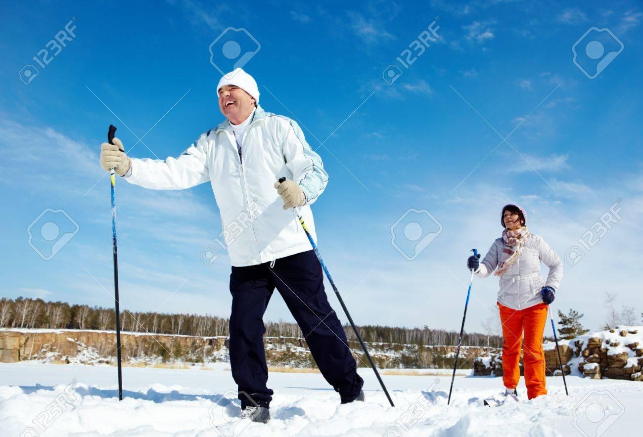 Portrait of mature couple skiing outside - 11920251