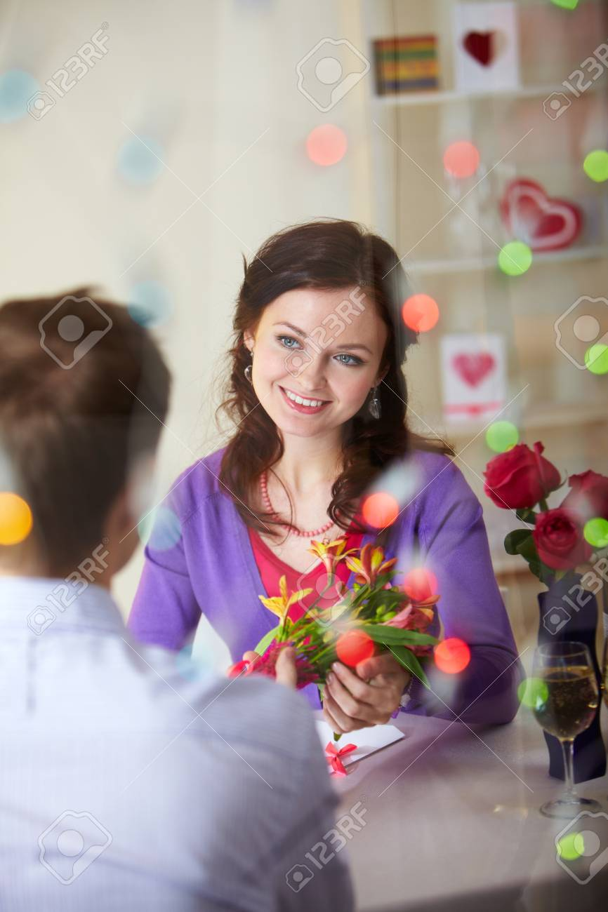A Young Man Giving Bouquet Of Flowers To Pretty Girlfriend Stock