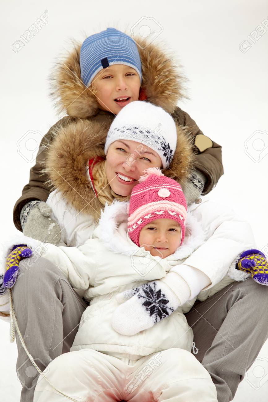 Happy kids and their mother sitting on sledge in park Stock Photo - 11938243