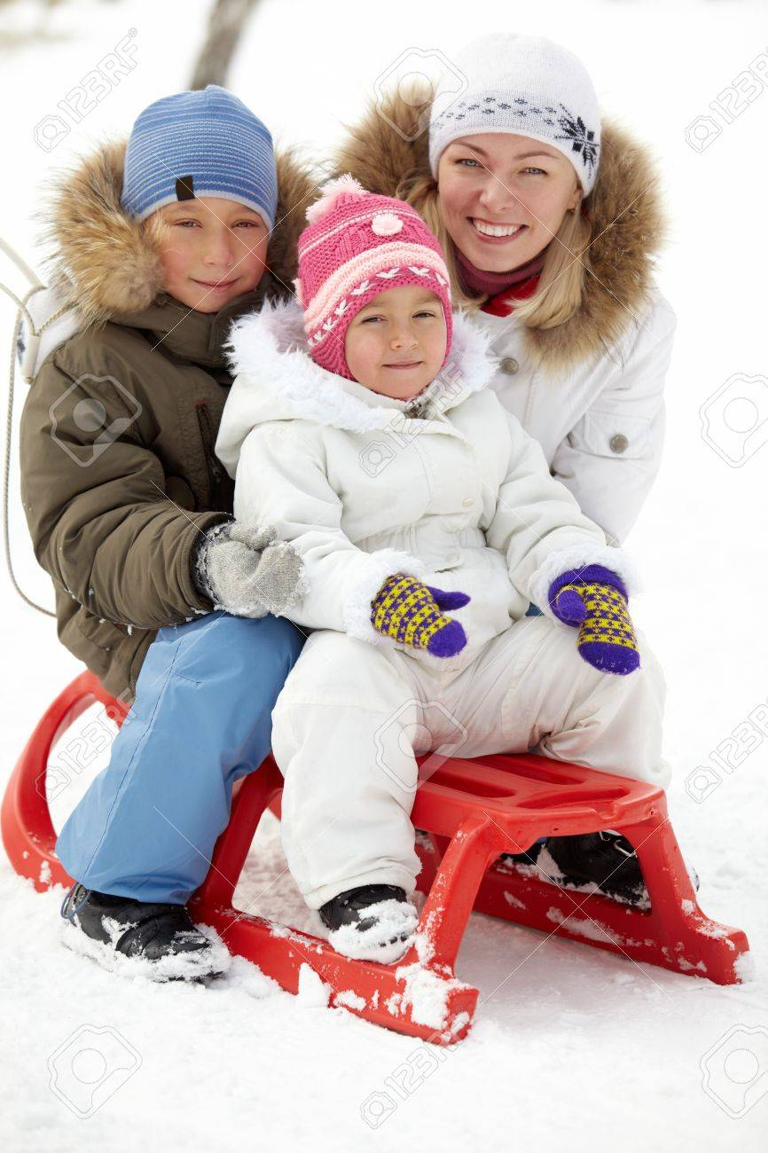 Happy kids sitting on sledge in park with their mother near by Stock Photo - 11938232