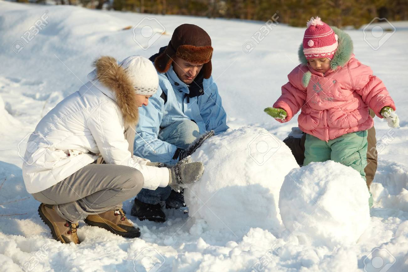 Portrait of family making snowman in park Stock Photo - 11938238