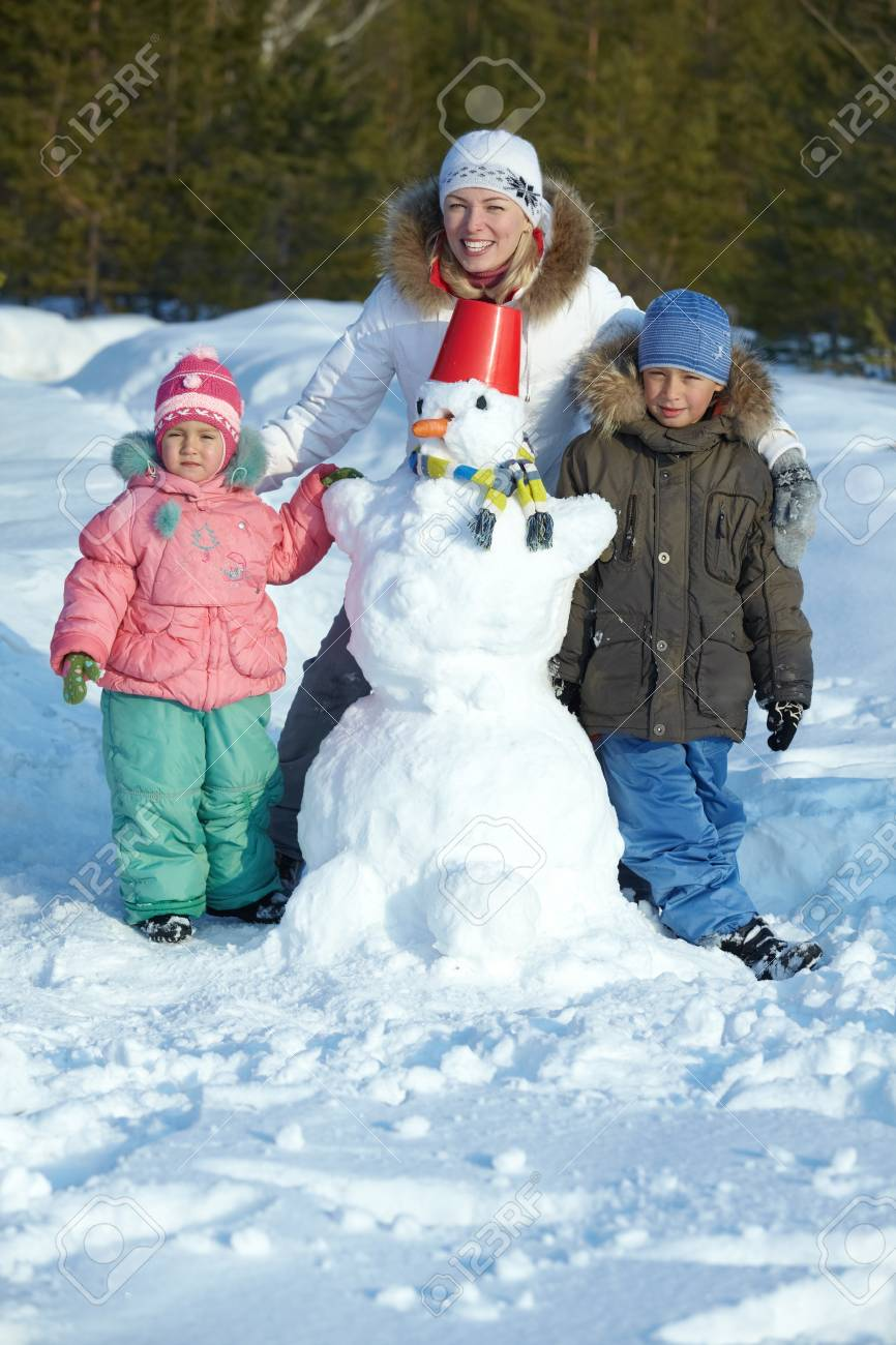 Portrait of happy family with snowman in park Stock Photo - 11938235