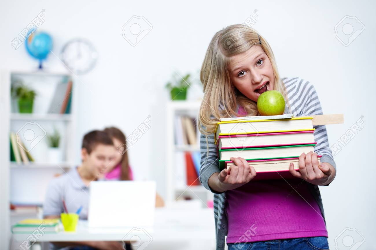 Portrait of cute teenage blonde with school objects looking at camera Stock Photo - 12026796