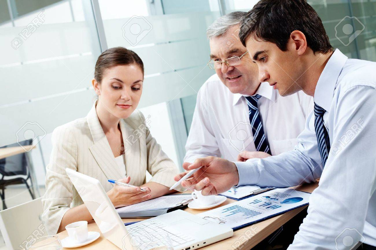 A business team of three sitting in office and planning work - 12061644