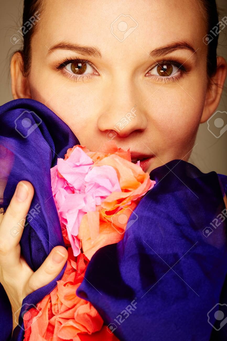 Gorgeous woman holds flower and looking at camera Stock Photo - 12324182