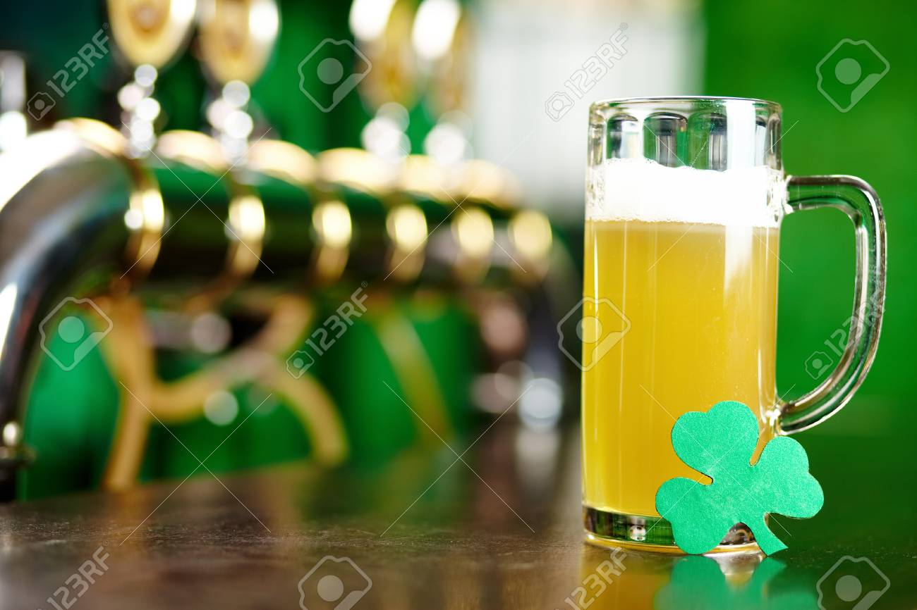 A glass of beer on a bar counter with a leaf of shamrock Stock Photo - 12326519