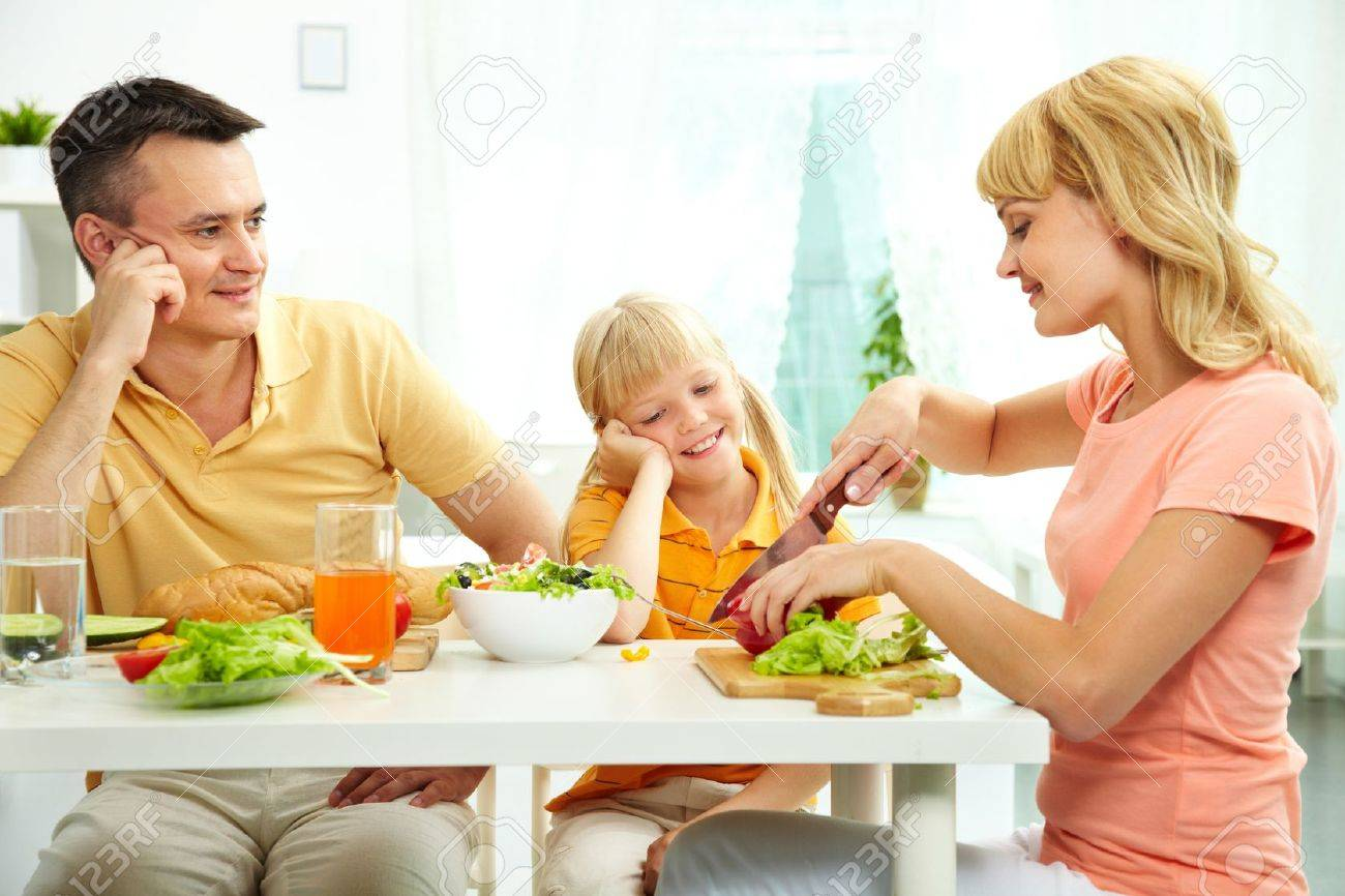 Family of three at table eating fresh vegetables - 12381188