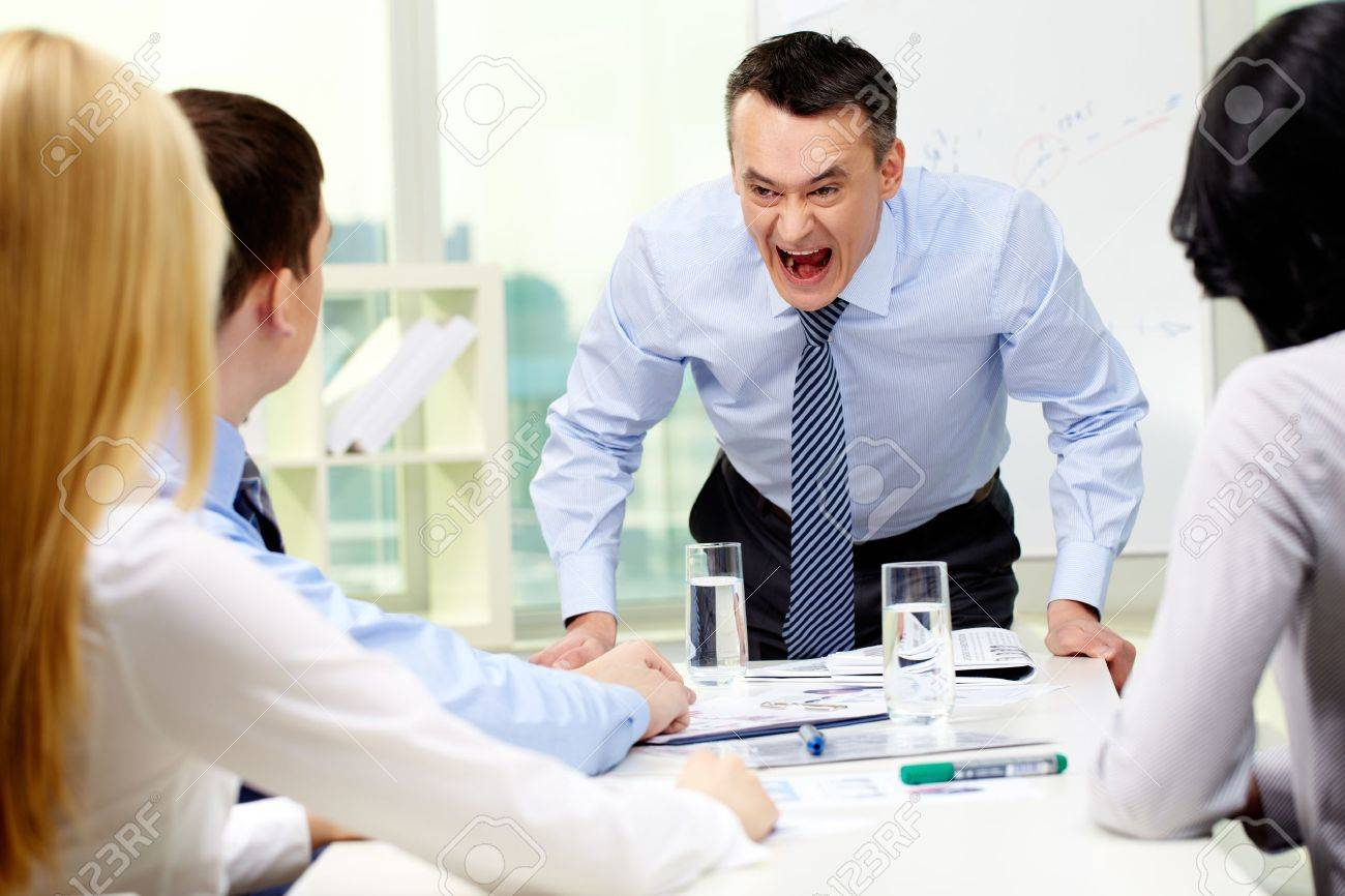 Angry businessman shouting at his workers with an expressive look Stock Photo - 12620660