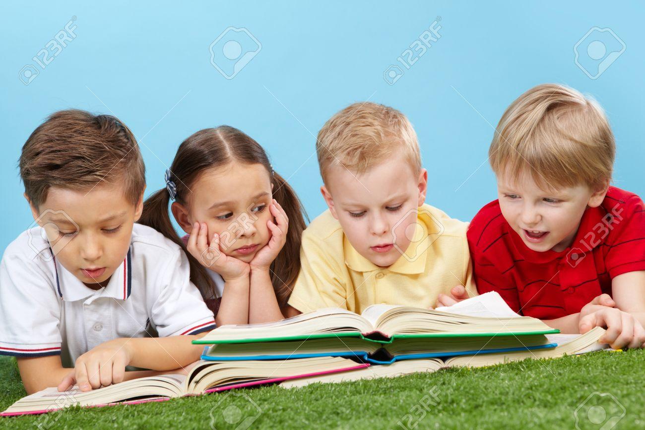 school children studying books lying on the grass stock photo