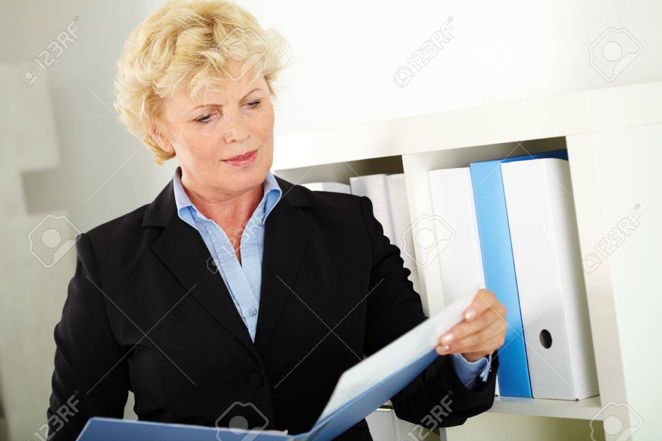 Portrait of middle aged businesswoman reading paper in office Stock Photo - 12872815