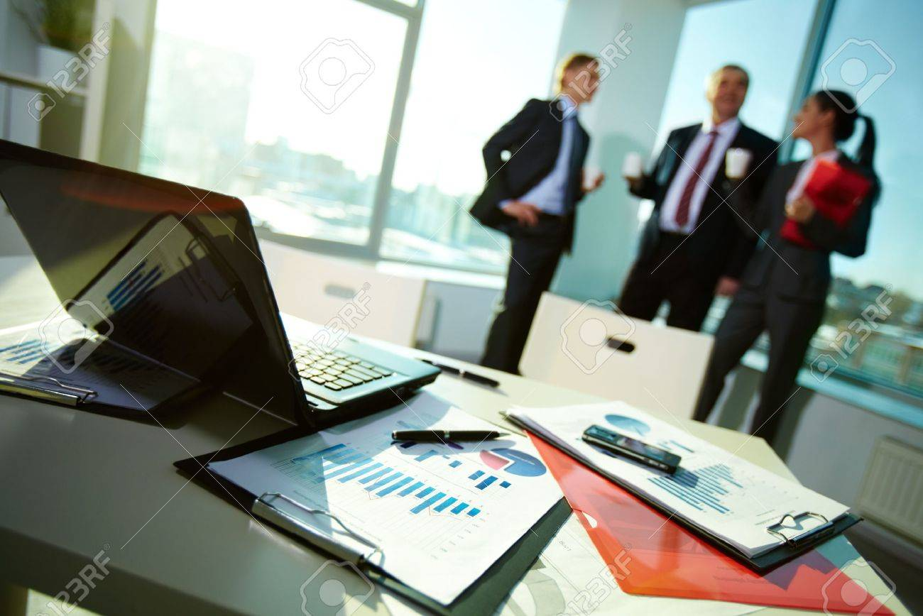 Image of business documents on workplace with three partners interacting on background Stock Photo - 12873178