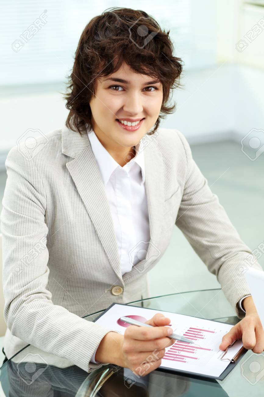 Vertical portrait of a business woman analyzing graphs and looking at camera with a smile Stock Photo - 13037944