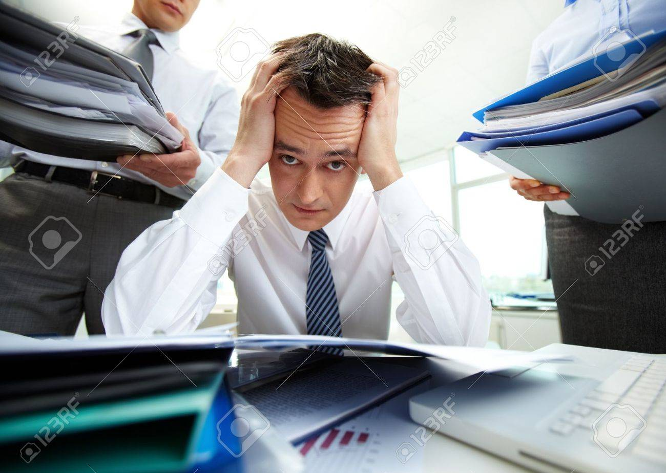 Perplexed accountant touching his head being surrounded by business partners with huge piles of documents Stock Photo - 13475843
