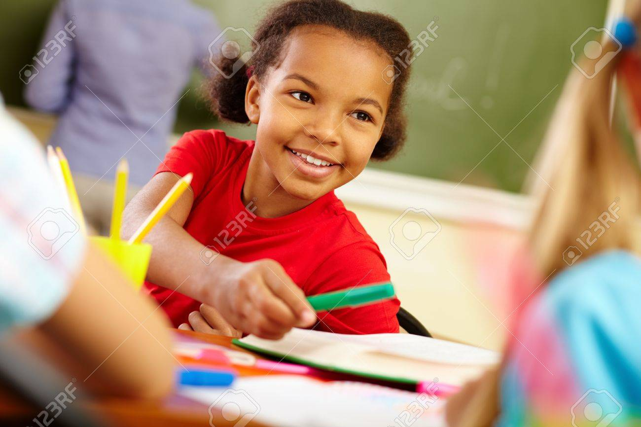 Portrait of cute girl giving crayon to classmate at lesson Stock Photo - 13631217