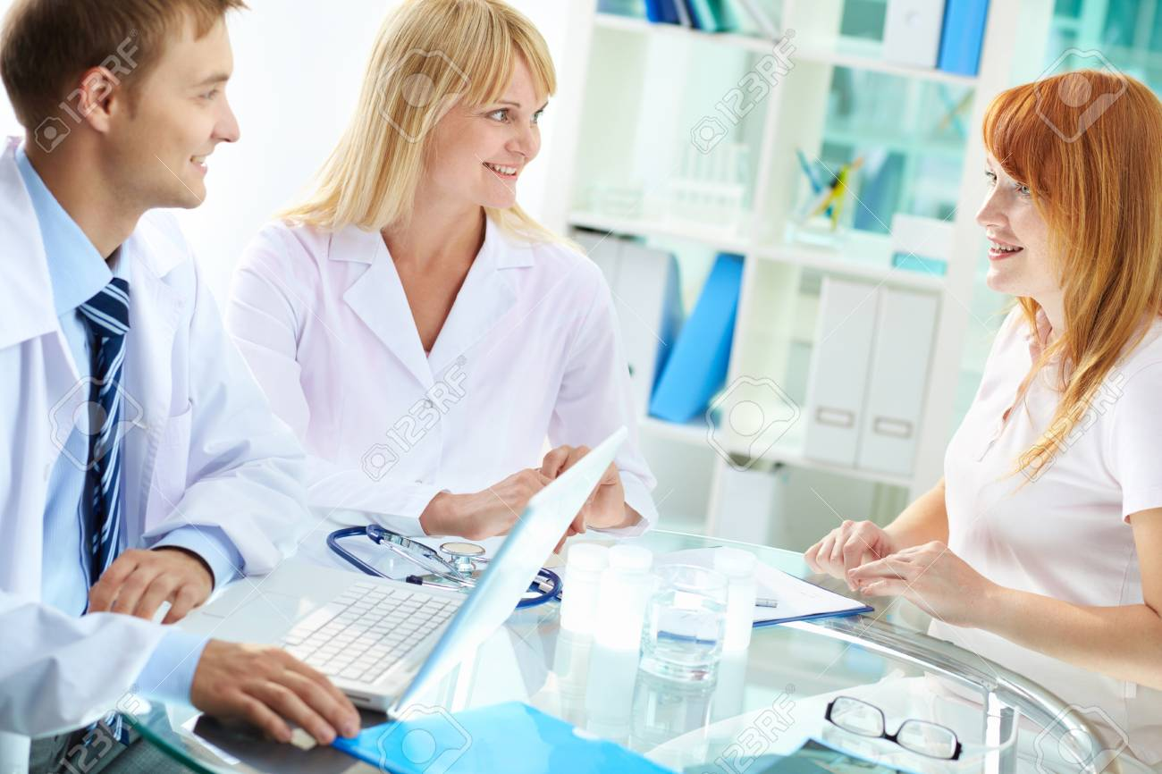 Portrait of confident practitioners consulting patient in hospital Stock Photo - 13949719