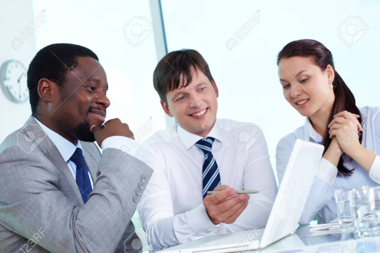 Three colleagues working with laptop at meeting Stock Photo - 14470077