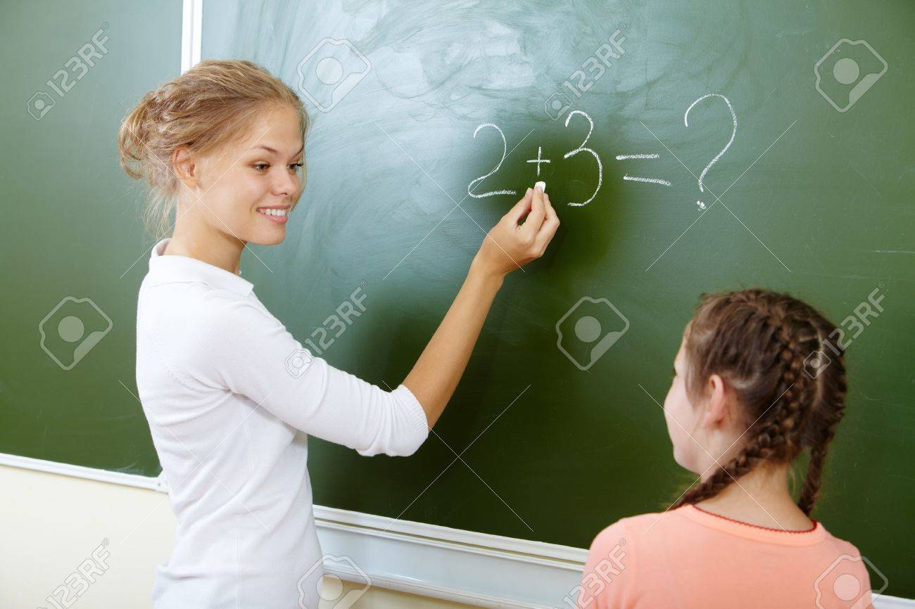 Photo of teacher writing sum on blackboard and looking at pretty pupil near by Stock Photo - 14644979