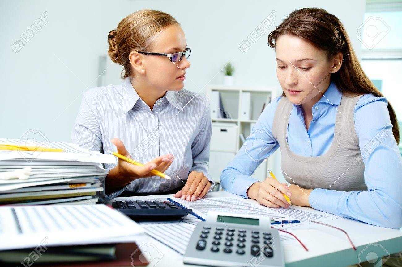 Portrait of young businesswomen interacting while working with papers in office Stock Photo - 14726928