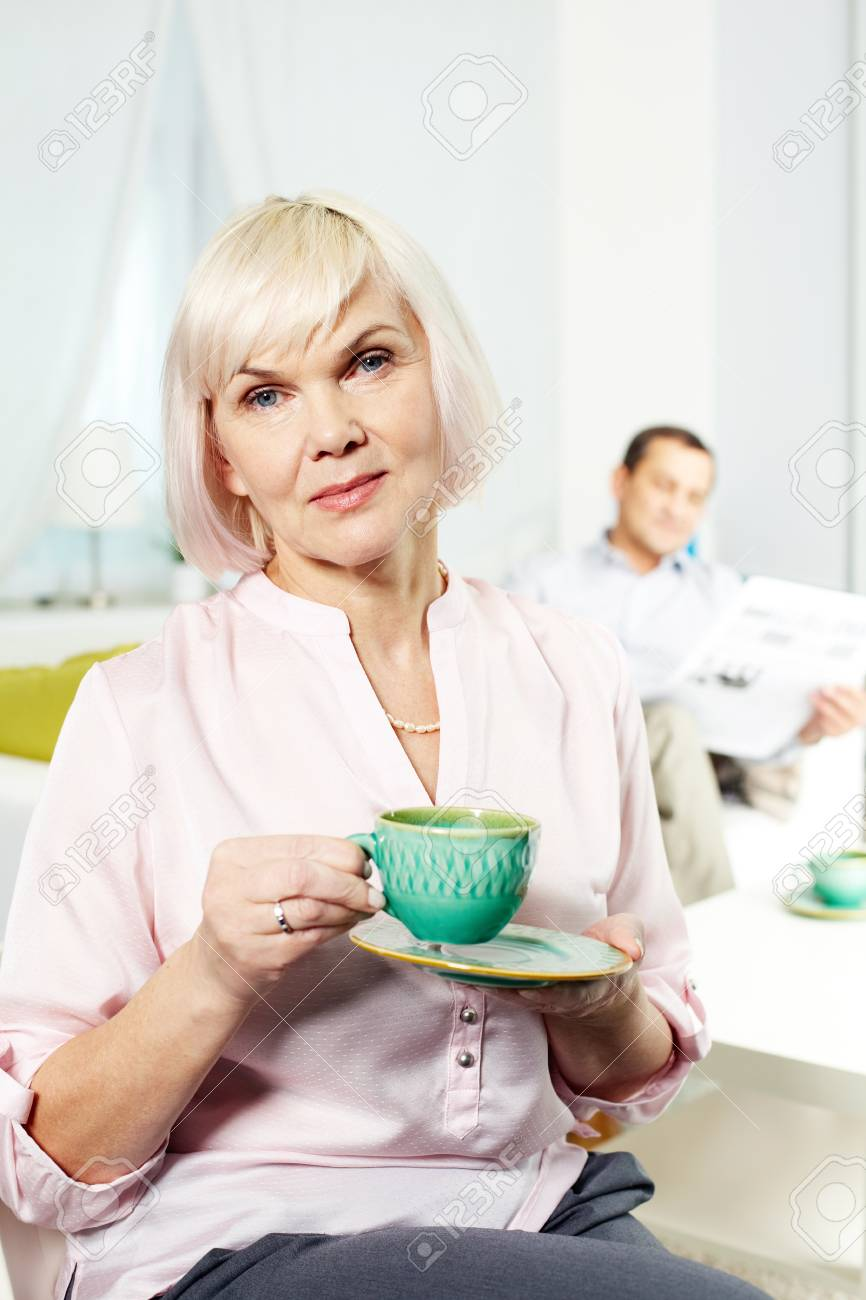 Portrait of mature woman with cup looking at camera on background of her husband Stock Photo - 14798628
