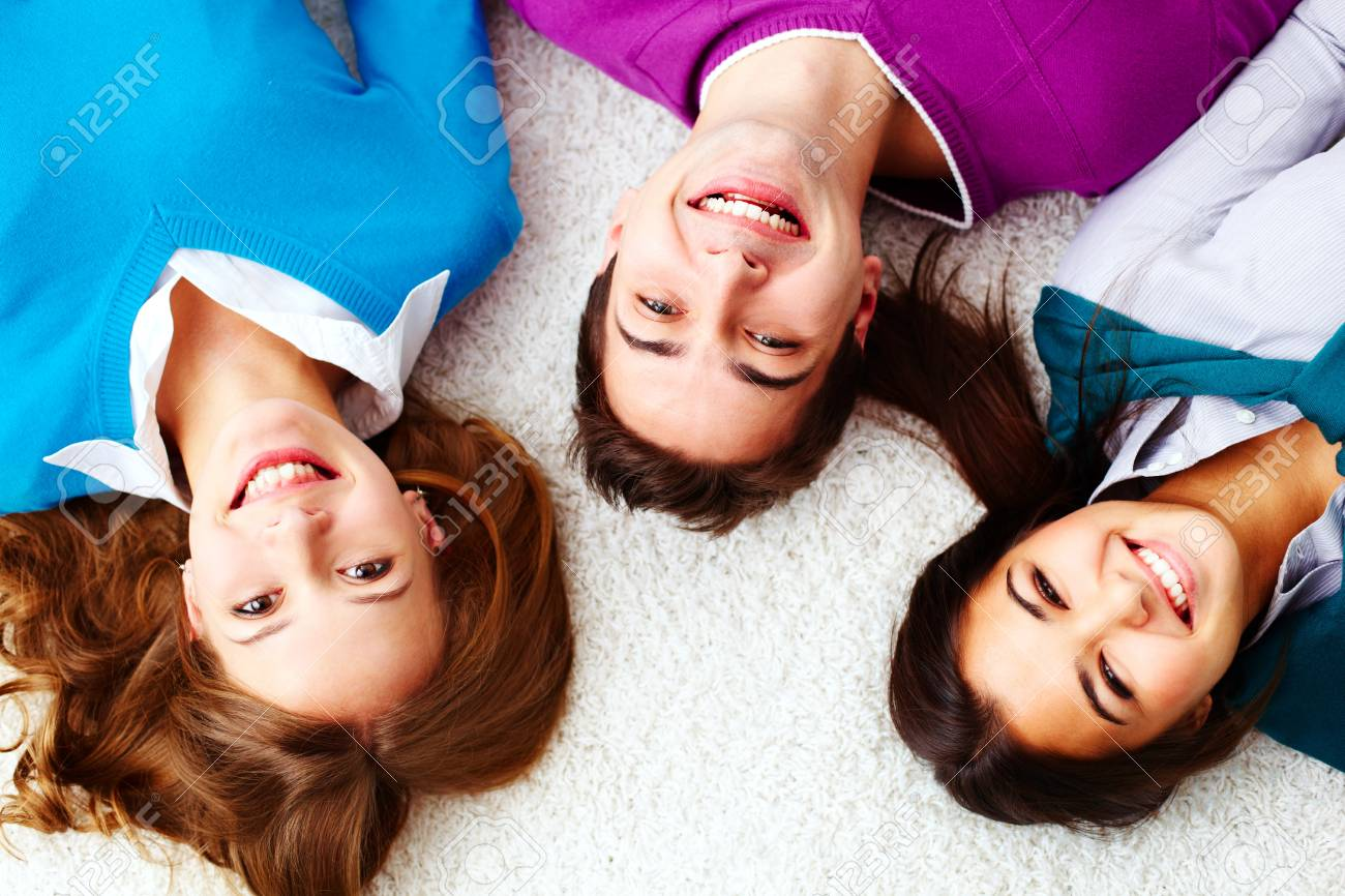 Above angle of attractive friends looking at camera and smiling Stock Photo - 15104279