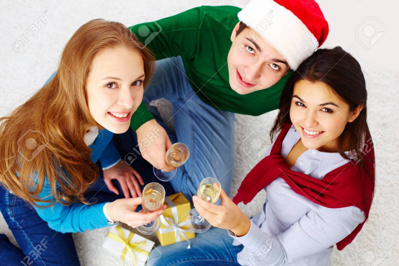 Above angle of attractive friends with champagne looking at camera and smiling Stock Photo - 15104263