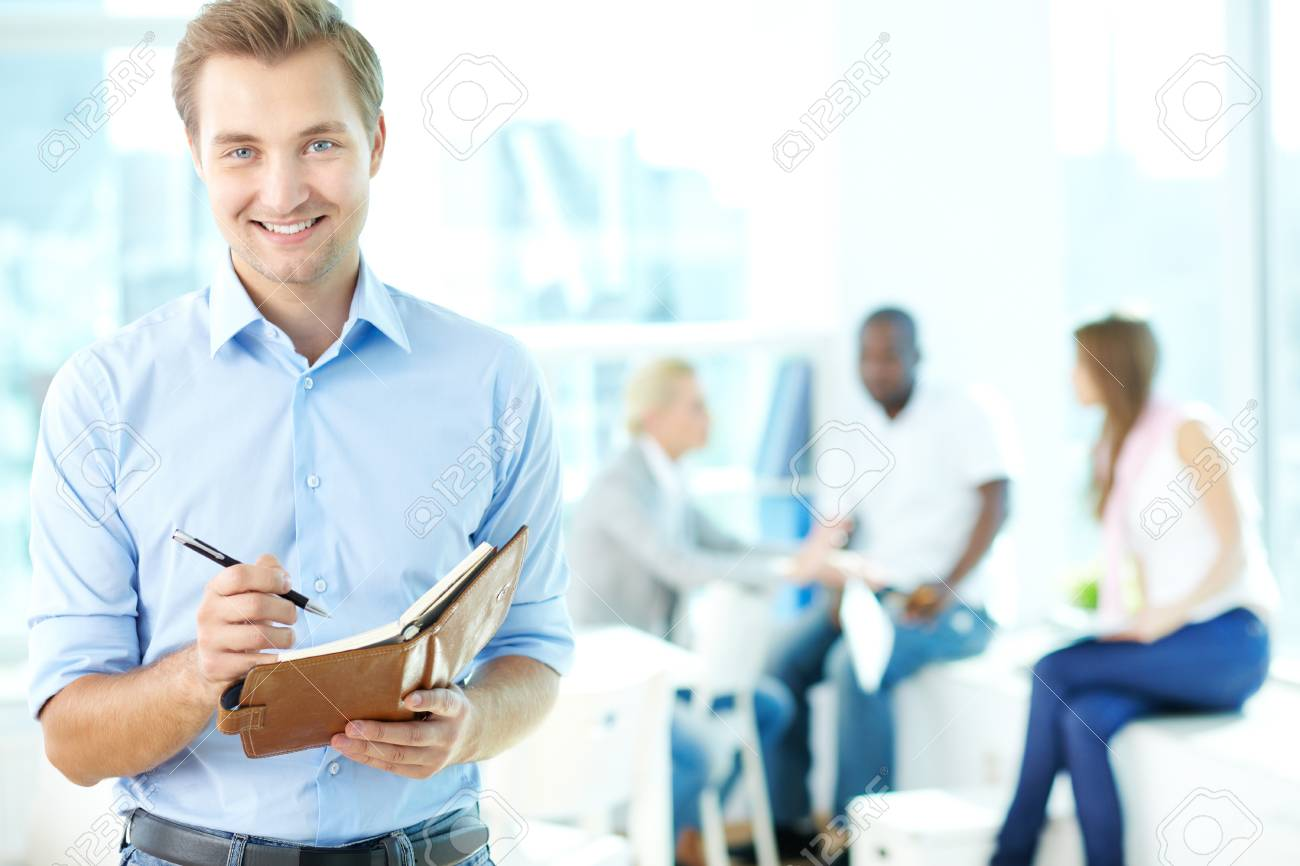 Portrait of happy man with pen and notepad looking at camera in working environment Stock Photo - 15436047