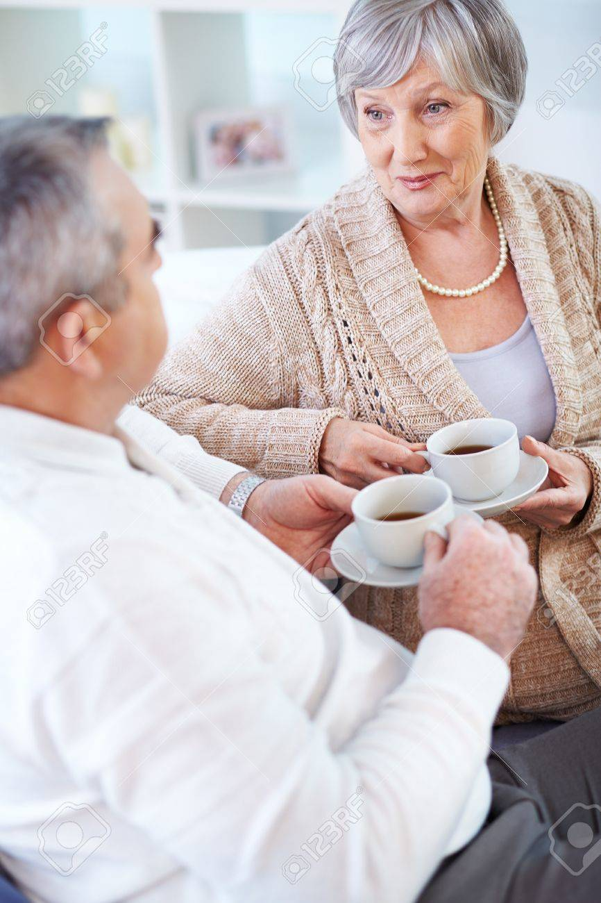Portrait of mature man and his wife drinking tea and interacting Stock Photo - 15610904