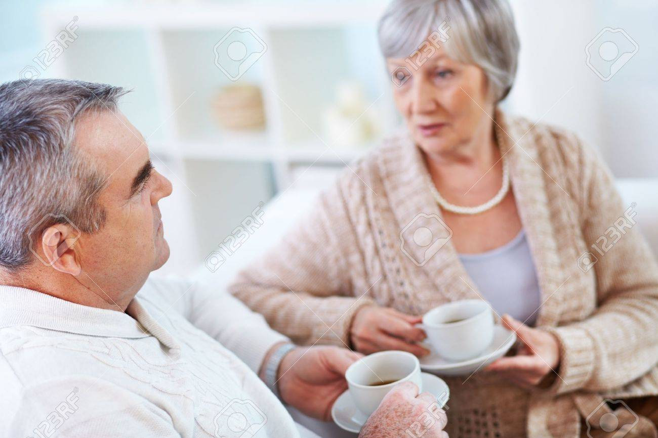 Portrait of mature man and his wife drinking tea and interacting Stock Photo - 15610920