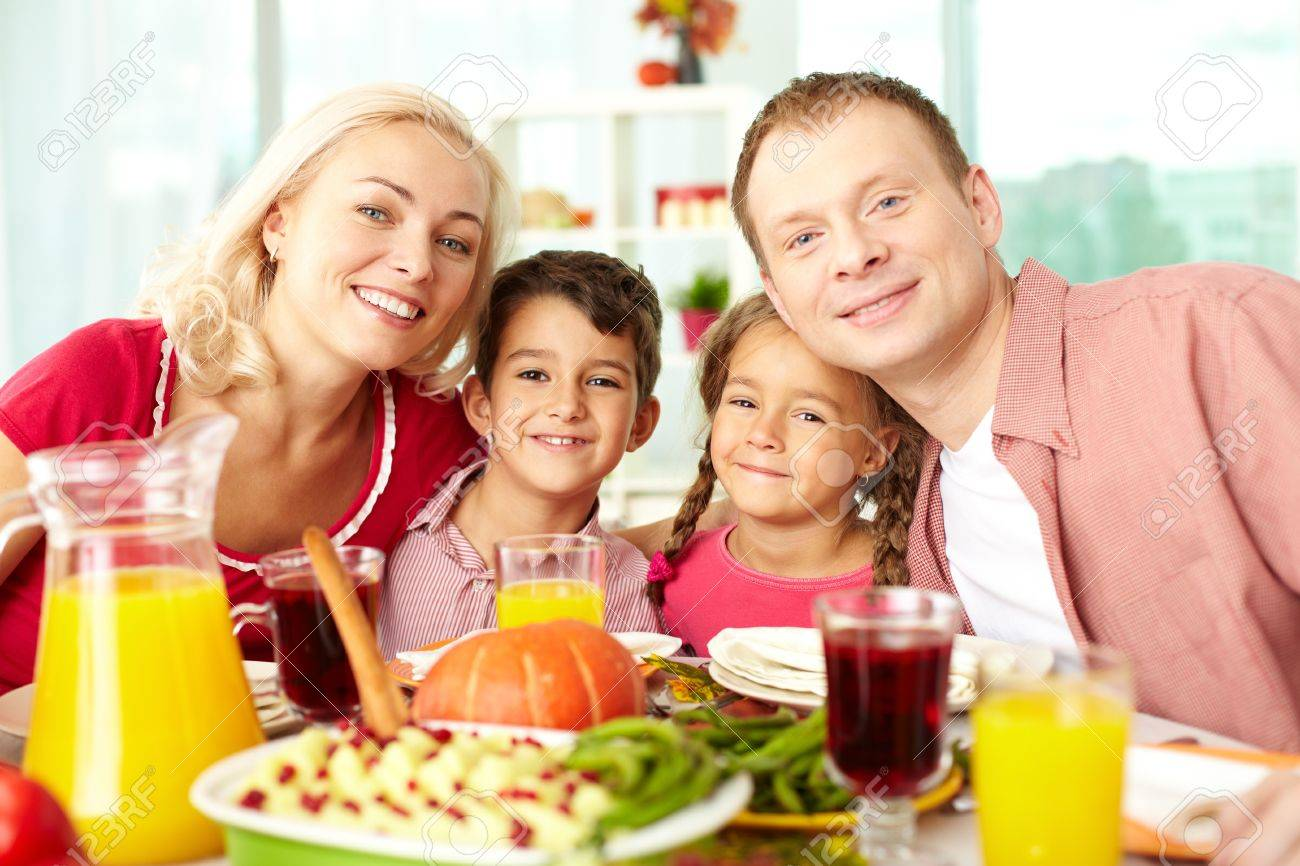 Portrait of happy family sitting at festive table and looking at camera Stock Photo - 15610639