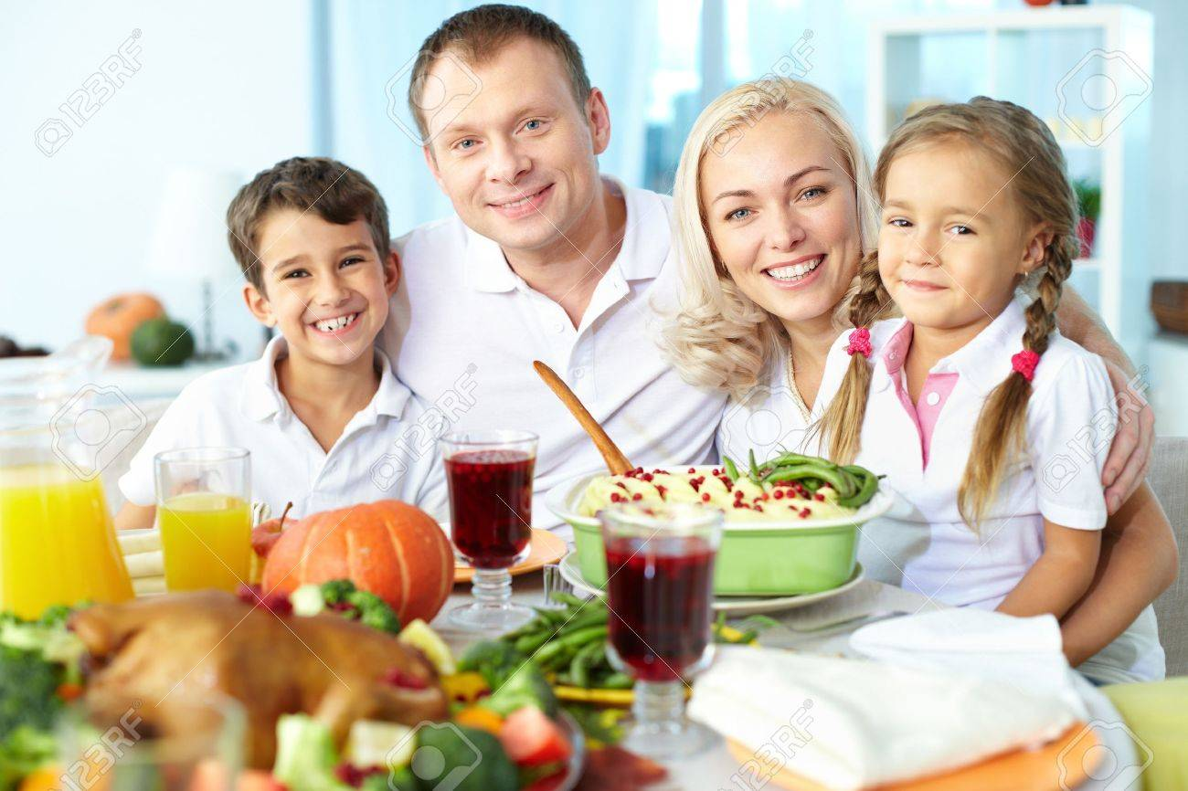 Portrait of happy family sitting at festive table and looking at camera Stock Photo - 15610807