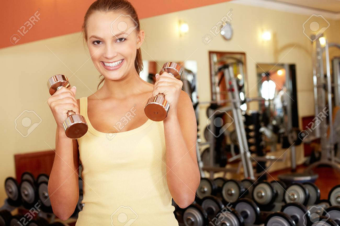 Portrait of pretty girl with dumbbells looking at camera in gym Stock Photo - 15725936