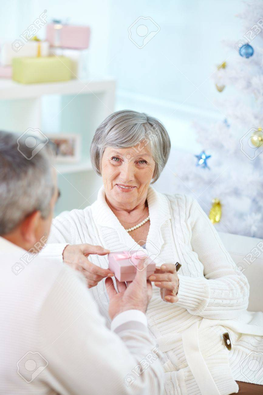 Portrait of mature woman holding small giftbox given by her husband Stock Photo - 15725939