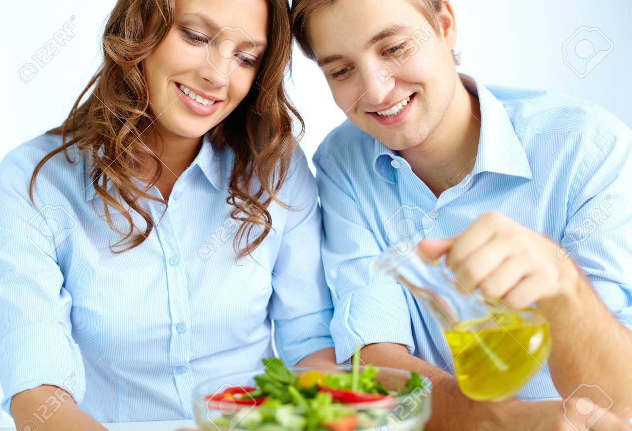 Happy man pouring oil into vegetable salad with his wife near by Stock Photo - 15978430