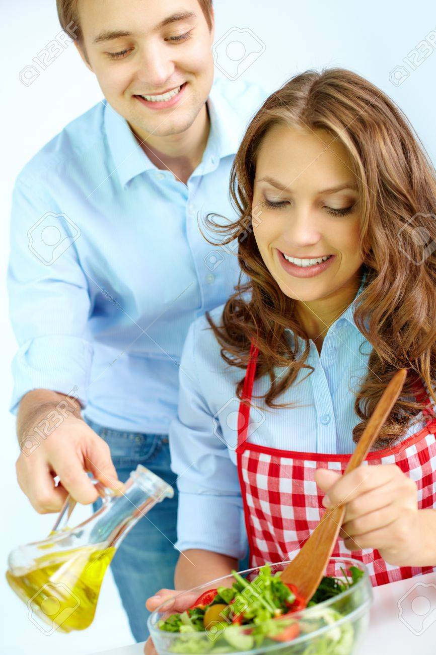 Happy man pouring oil into vegetable salad while his wife mixing ingredients Stock Photo - 15978464