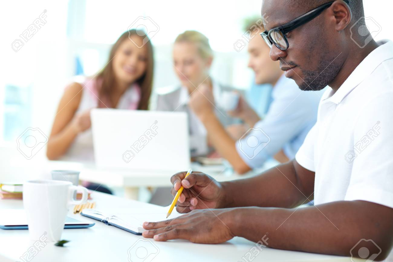 Portrait of cute African guy working with his partners on background Stock Photo - 16085679
