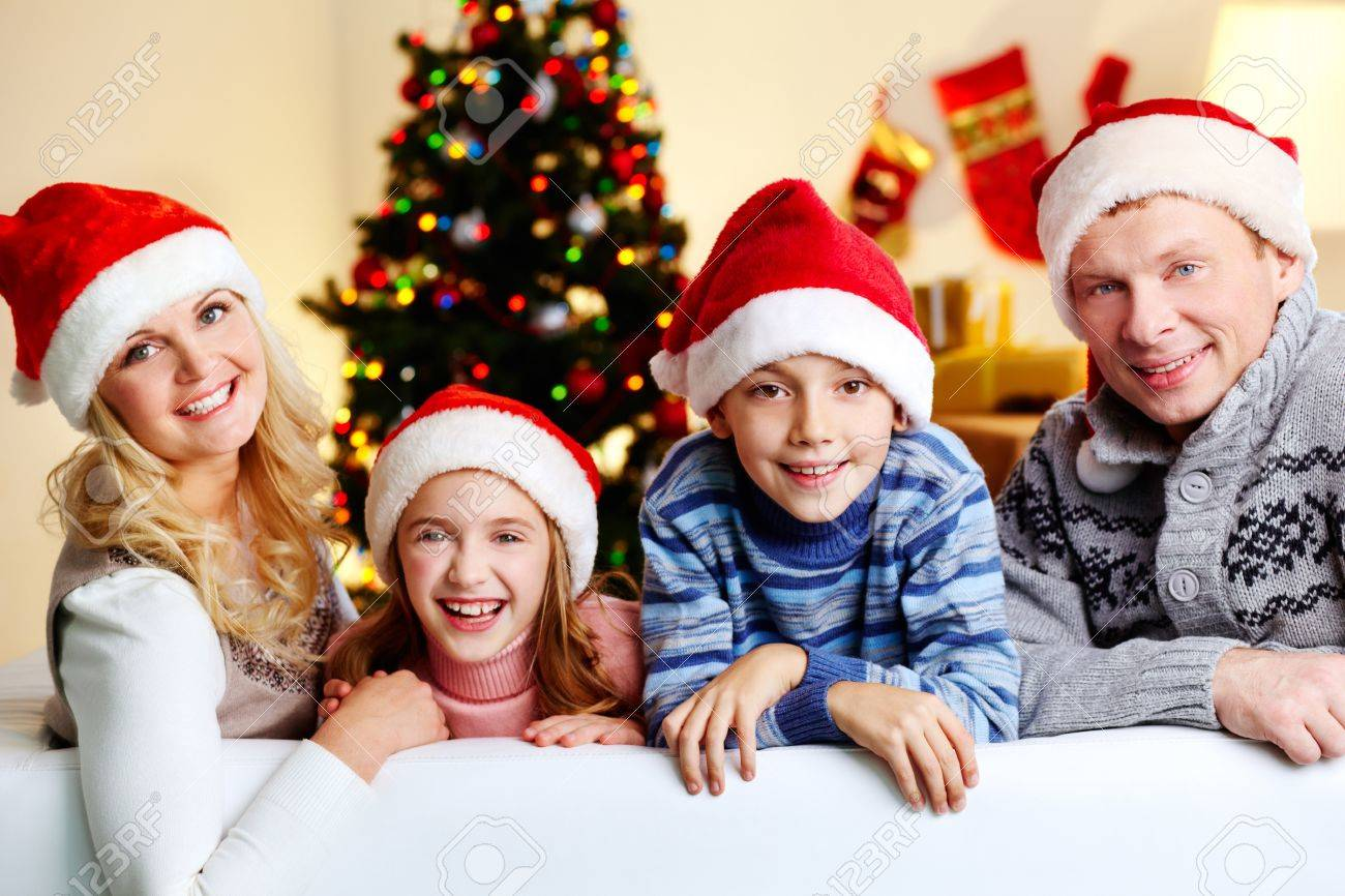 Portrait of four happy family members in Santa caps looking at camera with smiles Stock Photo - 16304947