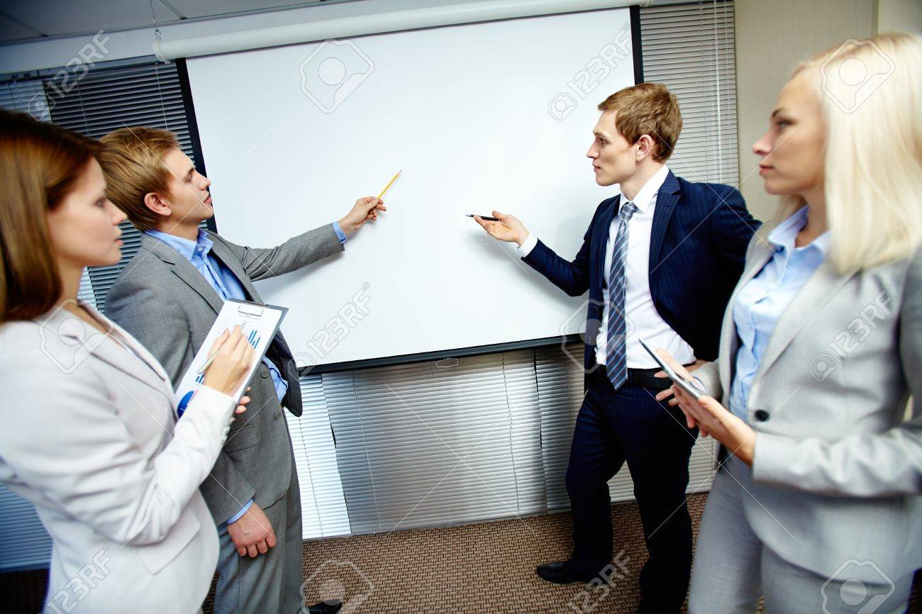 Two confident businessmen pointing at whiteboard while making speech at meeting Stock Photo - 16221803