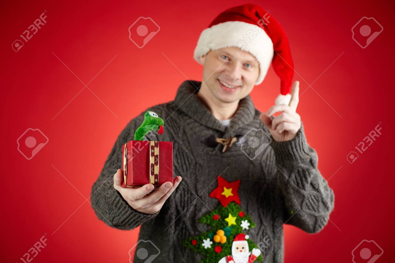 Portrait of happy man in Santa cap holding toy snake in open giftbox Stock Photo - 16611996